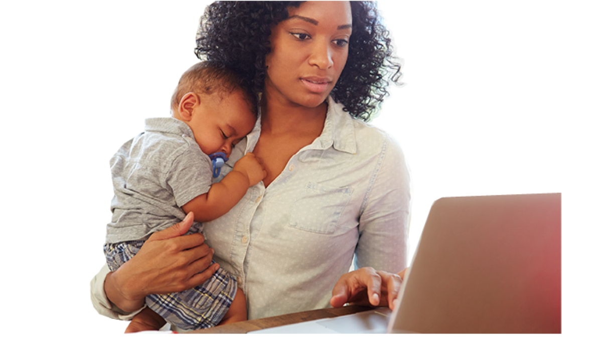 Mom looking at computer screen while carrying her young infant